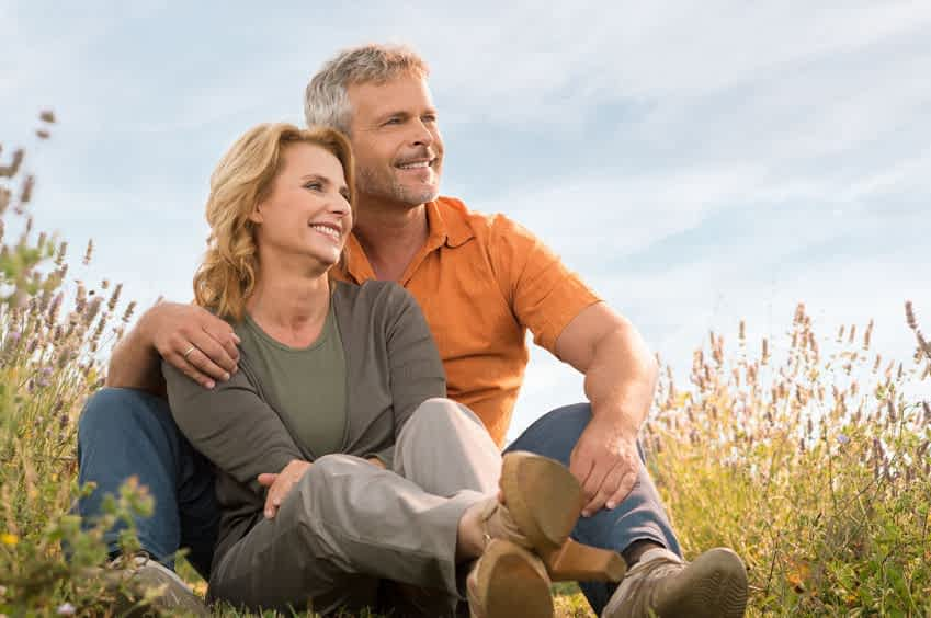 31178930 - portrait of a happy mature couple sitting in field and contemplate the future
